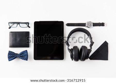 hipster personal stuff and objects concept - tablet pc computer, headphones, wallet, eyeglasses and wristwatch on table - stock photo