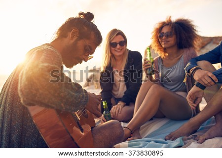 Hipster playing guitar for friends at the beach. Group of young people drinking beer and listening to music. - stock photo
