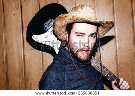 Hipster portrait of young man with guitar. - stock photo