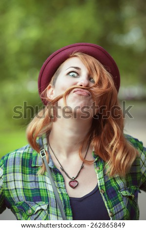 Hipster redhead woman making a moustache with her hair outdoor - stock photo