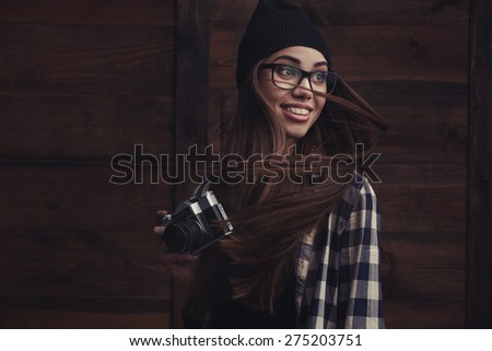 Hipster smiling girl in glasses and black beanie with vintage camera on the wooden background - stock photo
