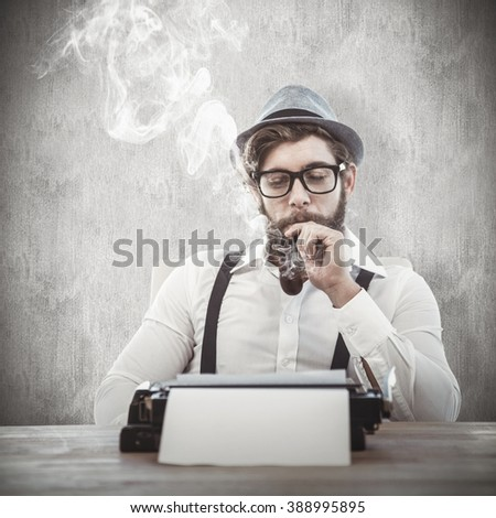 Hipster smoking pipe while sitting looking at typewriter against white and grey background