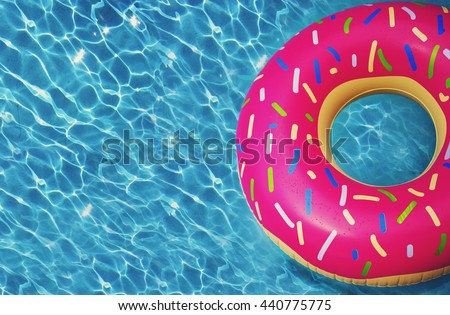 Hipster sprinkled donut float in sunny pool background straight down on bright clear pool water, vivid filter - stock photo