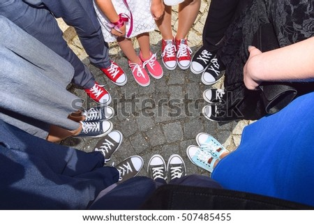 Hipster standing with sneakers in circle on concrete ground. Top view of cool youth white, black, red and pink gym shoes standing in circle.