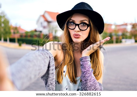 Hipster stunning woman making selfie , sending kiss, surprised funny emotions, natural make up, long blonde hairs, hipster hat and glasses, amity time, countryside. - stock photo