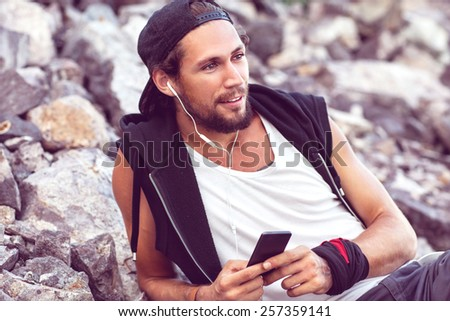 Hipster style boy. Fashion man sitting among the gray stone background is and listening to player - stock photo