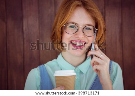 Hipster talking on phone having coffee on wooden background - stock photo