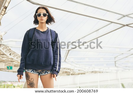 Hipster teenage girl in sunglasses with  tattoo