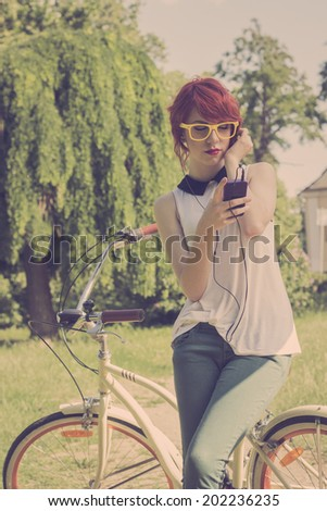 Hipster teenage girl on her vintage bike, listening to the music on her purple smart phone. Retro colors, toned image  - stock photo