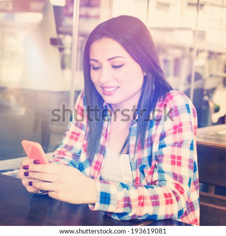 Hipster teenage mixed race girl in cafe with smart phone smiling and texting. Square image with instant filter look - stock photo
