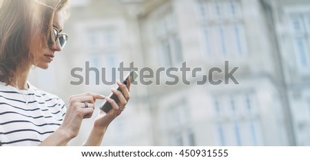 Hipster texting message on smartphone or technology, mock up of blank screen. Girl using cellphone on building castle background close. Tourist female hands holding gadget on blurred backdrop mockup