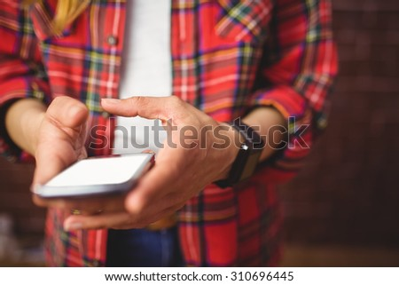 Hipster using her smartphone on red brick background - stock photo