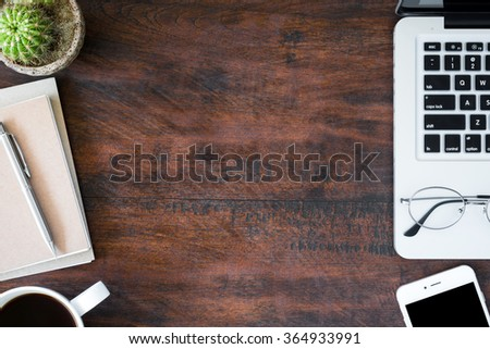 Hipster vintage office desk table with laptop, smartphone, eye glasses, notebooks, pen and a cup of coffee. Top view with copy space. - stock photo