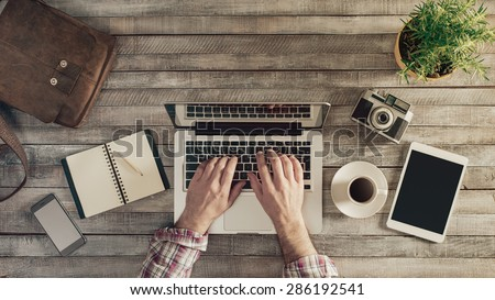 Hipster vintage wooden desktop top view, male hands typing on a laptop - stock photo