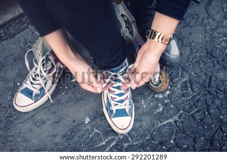 Hipster wearing sneakers, teenager tieing laces at sport shoes. Urban lifestyle with footwear and modern clothing. - stock photo