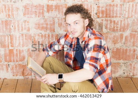 Hipster with a book in front of a brick wall. Handsome man reading in room. Modern lifestyle