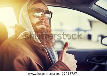 hipster with beard sitting in car giving thumbs up, shot with lens flare, retro filter and selective focus - stock photo