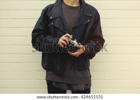 Hipster with vintage retro photo camera in hands - stock photo