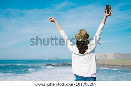 Hipster woman enjoy freedom on vacation travel. Successful funky girl raising arms towards the sea. - stock photo