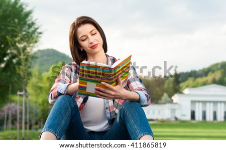 Hipster woman in casual clothes holding a book and reading in the park as freetime relaxation concept