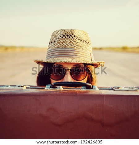 Hipster woman in hat and glasses looks out from vintage suitcase - stock photo