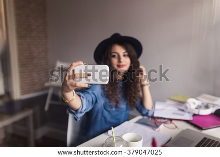Hipster woman taking selfie in her office. Shot trough window glass. Depth of field, selective focus - stock photo