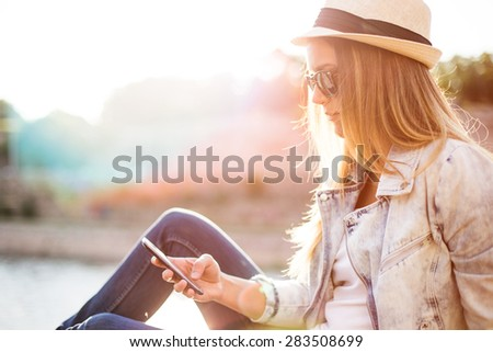 Hipster woman texting in sunset by the sea - stock photo