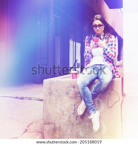 Hipster young Asian mixed race woman with headphones and smartphone. Beautiful casual teenage girl listening to music and texting wearing sunglasses. Square format image. Purple and blue toned filter. - stock photo