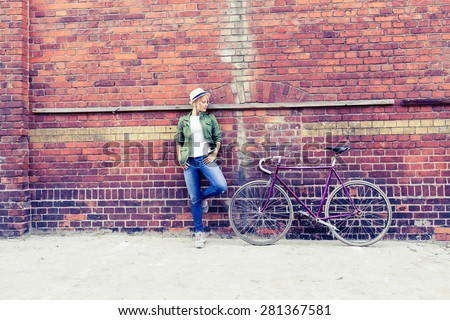 Hipster young beautiful girl with vintage road bike in city, urban scene. Beauty woman cycling on fixed gear bike in town, retro city street industrial background. - stock photo