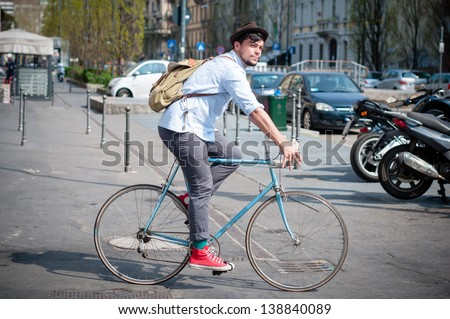 hipster young man on bike in the city - stock photo