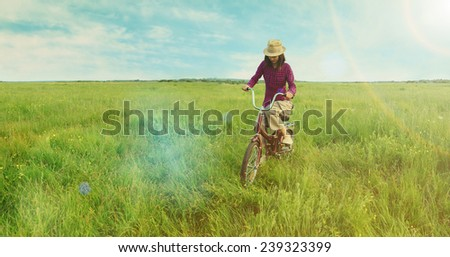 Hipster young woman cycling on green meadow in summer. Image with sunlight effect - stock photo