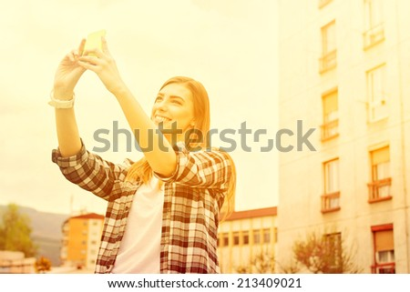 Hipster young woman taking a selfie outdoors. Beautiful young Caucasian modern woman taking a self portrait outdoors on sunny summer day in urban environment. Warm color filter. - stock photo