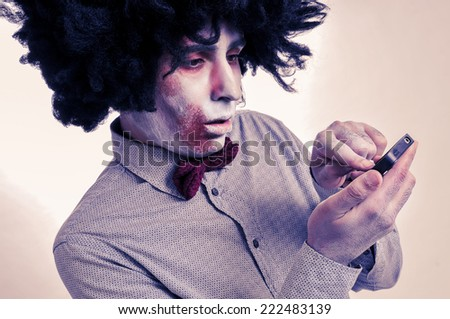 hipster zombie with an afro using a smartphone, with a filter effect - stock photo