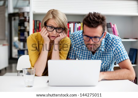 Hipsters in library working on laptop - stock photo