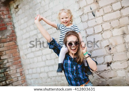 Hipsters woman in glasses keep on shoulders baby girl near brick wall background - stock photo