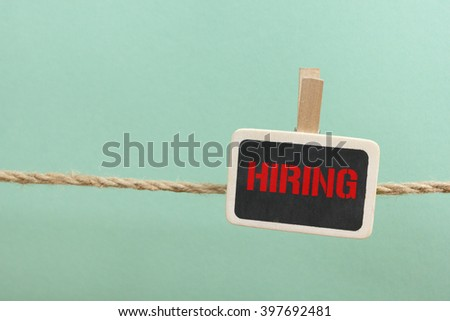 Hiring handwritten with white chalk on a blackboard at wooden background - stock photo