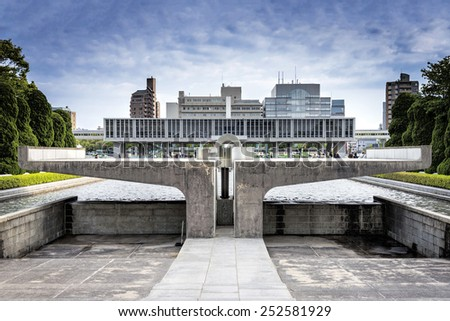 Hiroshima, Japan - April 27, 2014: View of  the Hiroshima Peace Memorial Museum behind the Peace Flame. The museum is located in Hiroshima Peace Memorial Park, and was established in 1955. - stock photo