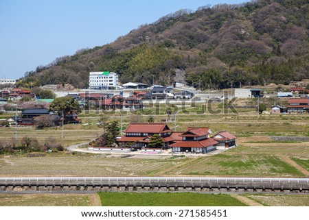 HIROSHIMA, JAPAN - CIRCA APRIL, 2013: Provincial area with traditional architecture is in Hiroshima prefecture, the view from the train window - stock photo