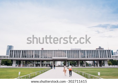 Hiroshima, Japan - July 10, 2015: View of the Hiroshima Peace Memorial Museum behind the Peace Flame. The museum is located in Hiroshima Peace Memorial Park, and was established in 1955. - stock photo