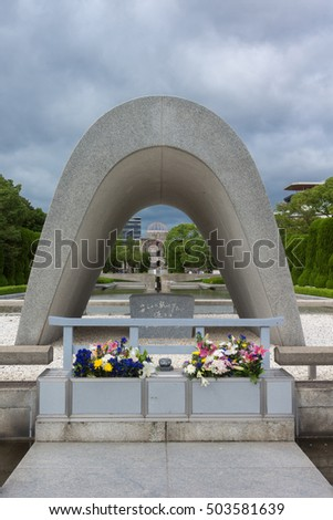 Hiroshima, Japan - September 20, 2016: The Memorial Cenotaph with the A-bomb ruin memorial at the far end it the Peace Memorial Park, looking over the pool and eternal flame. Flowers and cloudy sky.