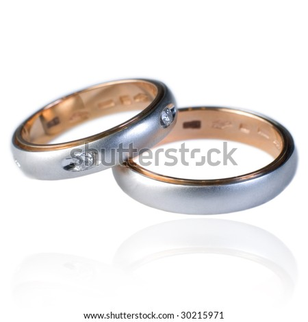 His and hers golden wedding bands, with diamonds. On a white background with soft reflection, isolated.
