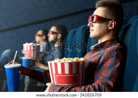 His chilling day. Handsome relaxed male wearing 3d glasses watching movies with popcorn and drinks