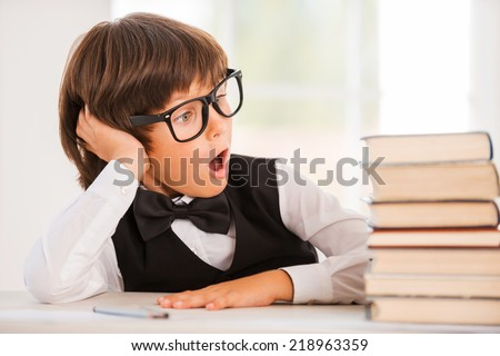 His favorite books. Excited young boy in shirt and bow tie sitting at the table and looking at book stack