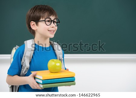 His first day at school. Cheerful little schoolboy holding the book stack and smiling while standing in front of blackboard - stock photo