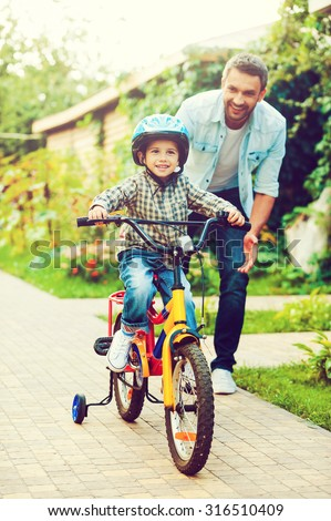 His first ride. Happy little boy riding bicycle and smiling while father helping him  - stock photo