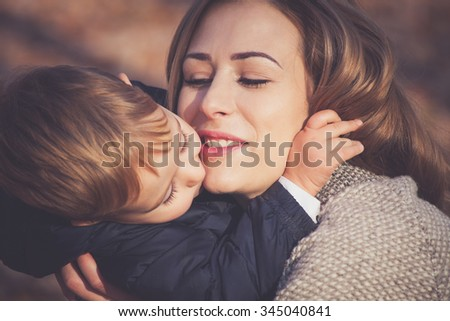 his mom is his greatest love, son and mom kissing and hugging, autumn day in park, closeup, selective focus - stock photo