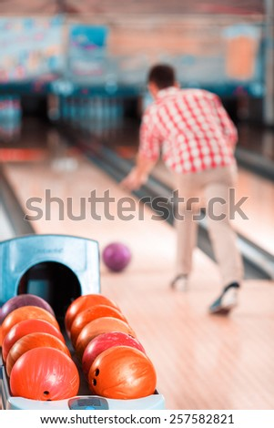 His perfect game. Rear view of young man playing bowling with balls in selective focus