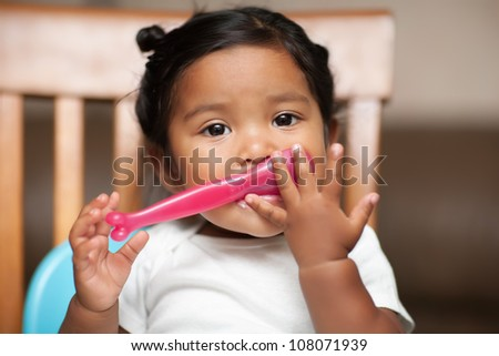 Hispanic baby girl learning to hold a spoon by herself - stock photo