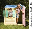 Hispanic boy and girl in outdoor playhouse smiling at viewer. - stock photo
