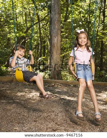 Hispanic boy and girl on swing set smiling at viewer. - stock photo